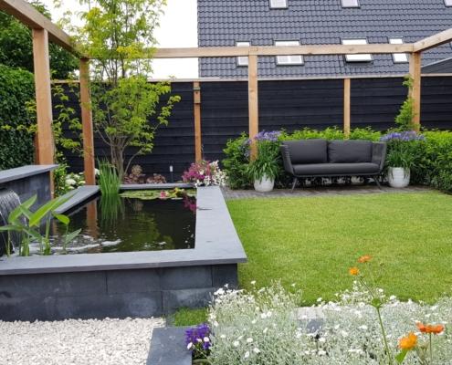 tuinaanleg met zwarte schuttingen en pergola